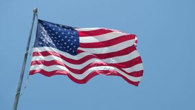 Amerikanska flaggan som vinkar i vinden mot blå himmel stock video