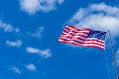Amerikanska flaggan som vinkar med molnig blå himmel på en solig dag fotografering för bildbyråer