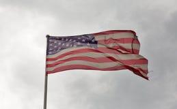 Amerikanska flaggan som vinkar mot en molnig himmel Arkivfoton