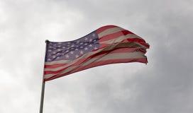 Amerikanska flaggan som vinkar mot en molnig himmel Fotografering för Bildbyråer