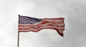 Amerikanska flaggan som vinkar mot en molnig himmel Arkivbilder