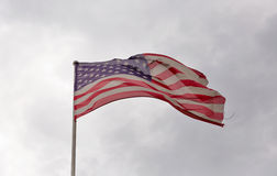 Amerikanska flaggan som vinkar mot en molnig himmel Arkivbild