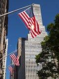 Amerikanska flaggan som vinkar proudly i brisen på New York City byggnad arkivbild