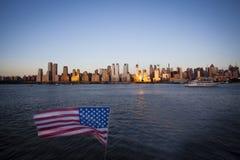 Amerikanska flaggan under självständighetsdagen på Hudson River med en sikt på Manhattan - New York City - Förenta staterna Arkivbild