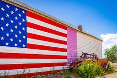 Amerikanska flaggan väggen av ett hus, gammalmodig lastbil på Route 66, tilldrar besökare från alla avvärlden Arizona arkivbild