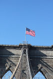 Amerikanska flaggan överst av den berömda Brooklyn bron Royaltyfri Fotografi