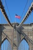 Amerikanska flaggan överst av den berömda Brooklyn bron Arkivbild