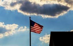Amerikanska flagganflyget mot en blå himmel med vita moln Royaltyfri Bild