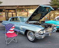 Amerikanska flaggangräsmattastol nära en klassisk bil på en Car Show Royaltyfri Foto