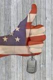 Amerikanska flagganhand med hundetiketter Arkivbild