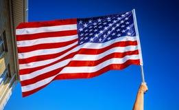 Amerikanska flagganinnehav i hand Royaltyfri Foto