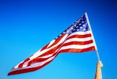 Amerikanska flagganinnehav i hand Royaltyfri Bild