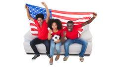 Amerikanska fotbollsfan i rött på soffan Arkivbilder