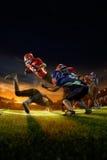 Amerikanska fotbollsspelare i handling på den storslagna arenan Arkivbilder