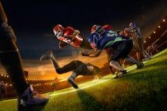 Amerikanska fotbollsspelare i handling på den storslagna arenan Arkivfoto