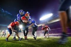 Amerikanska fotbollsspelare i handling på den storslagna arenan Arkivbild