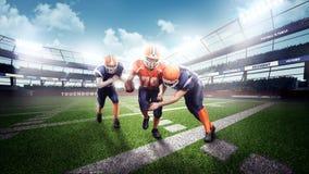 Amerikanska fotbollsspelare i handlingen på stadion Arkivfoto