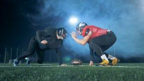 Amerikanska fotbollsspelare står mot varandra, klart att starta en lek 4K lager videofilmer