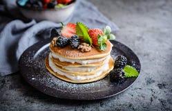 Amerikanska pannkakor med piskad kräm, jordgubbar, björnbär, valnötter och pudrat socker arkivbilder
