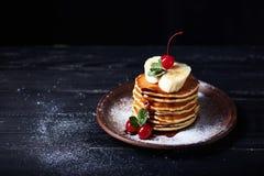 Amerikanska pannkakor på en platta med bananen, körsbäret och mintkaramellen arkivbilder
