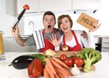 Amerikanska par i hemmastatt kök för spänning i matlagningförklädet som frågar för frustrerad hjälp fotografering för bildbyråer