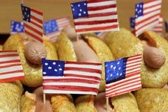Amerikanska varmkorvar med små amerikanska flaggan stänger plan, bullen och korven Royaltyfri Bild
