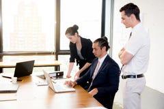 Amerikanskt folkaffärslag som har genom att använda bärbara datorn under ett möte Arkivbild