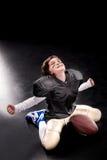 Amerikanskt fotbollsspelaresammanträde för gladlynt pojke med bollen och att triumfera arkivbilder