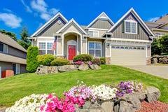 Amerikanskt hus med härligt landskap och livliga blommor Royaltyfri Fotografi