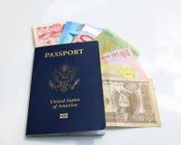 amerikanskt pass och internationella valutor Arkivbild