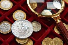 Amerikanskt silverdollar och förstoringsglas Arkivbild