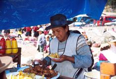 Amerindian woman. Amerindian food vendor in traditional dress at the market, Perù. Amerindians constitute around 45% of the total population. The two major Royalty Free Stock Photo