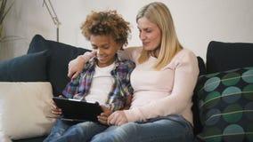 Amerykańska kobieta i wielo- etniczna chłopiec siedzimy na kanapie wpólnie i oglądamy online zdjęcie wideo