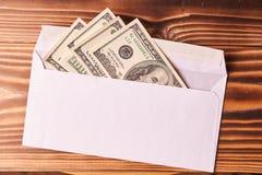 Amerykańscy dolary w białej kopercie Drewniany tło fotografia stock