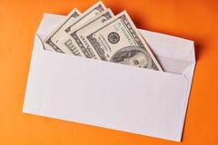 Amerykańscy dolary w białej kopercie Pomarańczowy tło fotografia stock