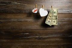 Amerykańscy dolary w dwa banknotach i serca dla dużego sprzedaży obwieszenia z clothespins Wakacyjna sprzedaż obraz stock
