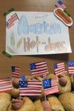 Amerykańscy hot dog z małymi flaga amerykańskimi zamknięty plan, babeczka, kiełbasa i inskrypci amerykańscy hot dog na papierze, zdjęcia royalty free