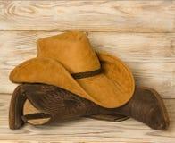 Amerykańscy Zachodni kowbojscy buty i kapelusz na drewnianym tekstury tle fotografia stock