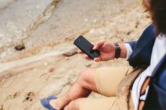 Amerykański Brodaty mężczyzna używa telefon blisko rzeki Fotografia Stock