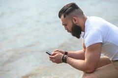 Amerykański Brodaty mężczyzna używa telefon blisko rzeki Obraz Stock