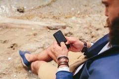 Amerykański Brodaty mężczyzna używa telefon blisko rzeki Zdjęcie Stock