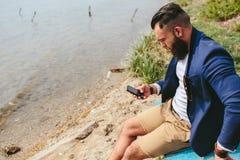 Amerykański Brodaty mężczyzna używa telefon blisko rzeki Zdjęcia Royalty Free