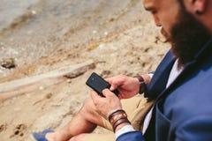 Amerykański Brodaty mężczyzna używa telefon blisko rzeki Obrazy Royalty Free