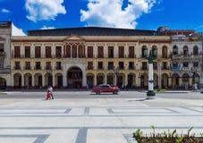 Amerykański czerwony Oldtimer drived na głównej ulicie w Hawańskim Kuba z uliczną scenerią - Seria Kuba 2016 reportaż Zdjęcia Royalty Free