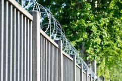 Amerykański drutu kolczastego ogrodzenie z ostrzami i ostrze punktami, fotografia stock