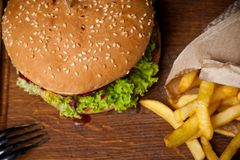 Amerykański hamburger i francuzów dłoniaki na drewnianej desce Fotografia od wierzchołka zdjęcia stock