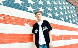 Amerykański nastoletni chłopak Przed flaga amerykańska Malującą ścianą zdjęcia royalty free