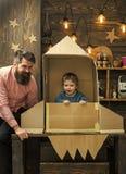 amerykański sen Chłopiec sztuka z tata, ojciec, mały kosmonauta siedzi w rakiecie robić z kartonu Dziecko chłopiec śliczna sztuka zdjęcia royalty free