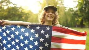 Ameryka?ski ucze? trzyma du?? USA flag?, ono u?miecha si? i Zako?czenie portret USA dzie? niepodleg?o?ci zdjęcie wideo