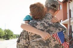 Amerykańskiego żołnierza przytulenie z jego synem outdoors zdjęcia royalty free